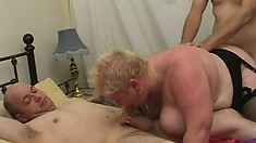 Fat mature blonde in black stockings gets fucked by two guys on the bed